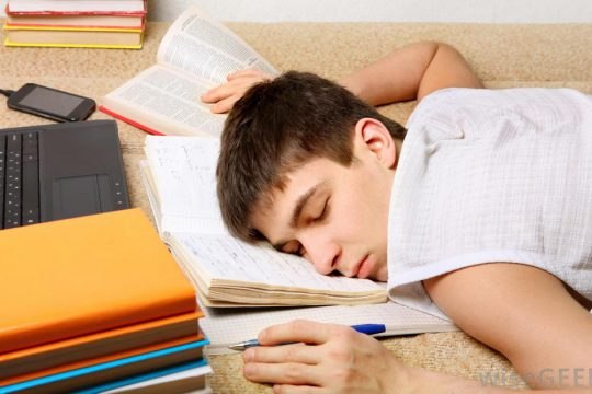 boy-asleep-on-books-with-computer